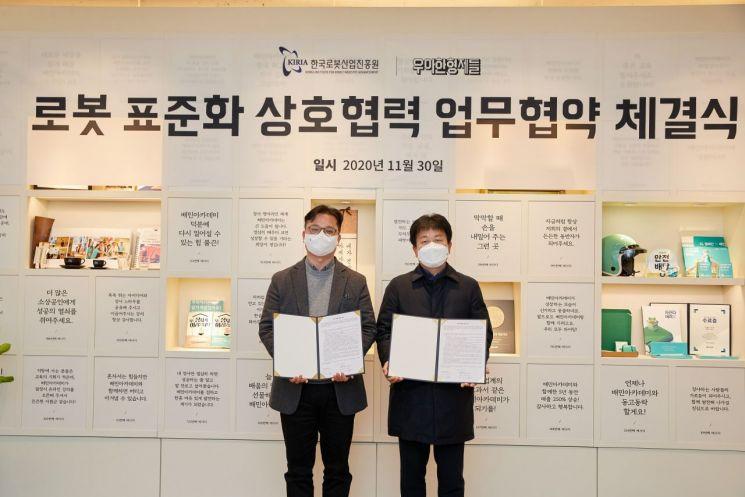 김요섭 우아한형제들 로봇사업실 이사(왼쪽)와 우종운 한국로봇산업진흥원 인증평가사업단장이 '로봇 표준화 상호협력 업무협약(MOU)'을 체결하고 기념촬영을 하고 있다.