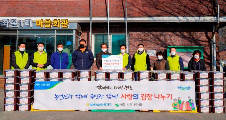 지난달 30일, 강원 홍천 소재 왕대추마을에서 NH농협금융지주 김형신 부사장(사진 오른쪽 5번째) 등 임직원 봉사단 및 왕대추마을 주민들이 김장김치 전달 행사를 하고 있다.