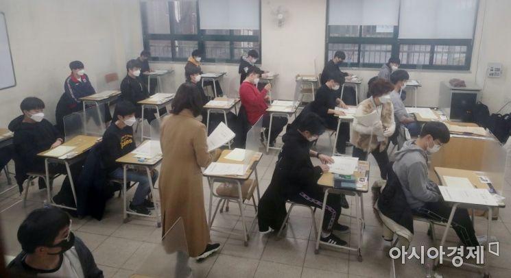 2021학년도 대학수학능력시험이 치러진 3일 오전 서울 종로구 경복고등학교에 고사장에서 감독관들이 수험생들에게 시험지를 나눠주고 있다.   신종 코로나바이러스 감염증(코로나19) 여파로 2주 늦춰진 이번 수능은 역대 최소인 49만3433명이 응시한 가운데 전국 86개 시험지구 1383개 시험장에서 일제히 치러진다. 2020.12.3