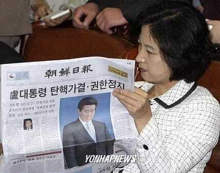 2004년 3월13일 추미애 당시 민주당 의원이 노무현 전 대통령에 대한 탄핵 소추가 의결됐다는 내용이 보도된 신문을 보고 있다. [이미지출처=연합뉴스]