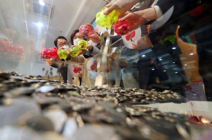 4일 오후 대구 동구청에서 열린 '100원의 큰사랑 나눔 실천행사'에서 배기철 동구청장 등 참석자들이 저금통에 모아온 100원 동전을 한곳에 모으고 있다. [이미지출처=연합뉴스]
