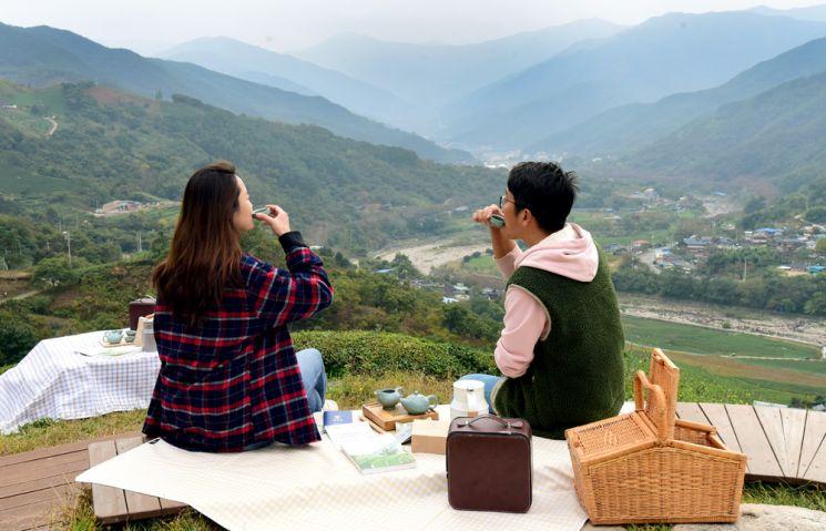 여행객이 차세트가 꾸려진 다구를 펼쳐 놓고 하동 화개천이 굽이쳐 섬진강으로 흘러드는 산중턱 차밭에 앉아 차를 마시며 풍경을 즐기고 있다.