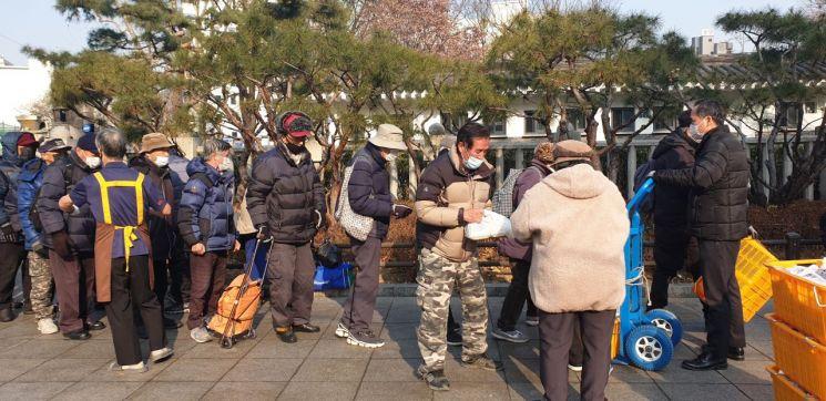 지난 26일 서울시 종로구 탑골공원 담장 옆에서 마스크를 쓴 노인들이 도시락 배식을 받기 위해 밀착해 줄을 서있다.(사진=류태민 기자)