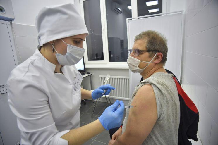 러시아 모스크바에서 한 의료진이 남성 노인에게 '스푸트니크 V' 코로나19 백신을 접종하고 있다. [이미지출처=AP연합뉴스]