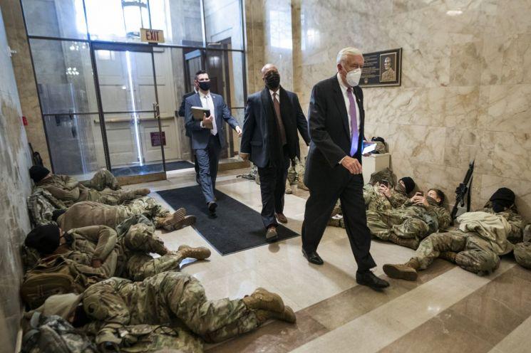 민주당 하원 원내대표인 스터니 호이어 의원이 의사당내에서 휴식중인 주 방위군들 사이를 지나 회의장으로 향하고 있다. [이미지출처=EPA연합뉴스]