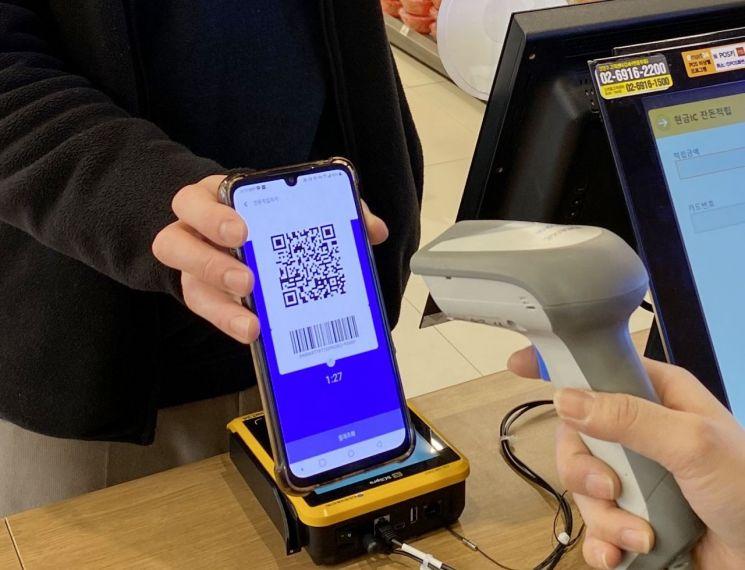 이마트24에서 고객이 모바일현금카드 QR코드를 통해 잔돈을 입금받고 있다.
