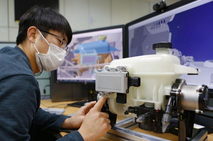 현대위아 의왕연구소에서 새롭게 개발한 전기차 전용 열관리시스템 '냉각수 분배·공급 통합 모듈'을 살펴보고 있다.(사진=현대위아)