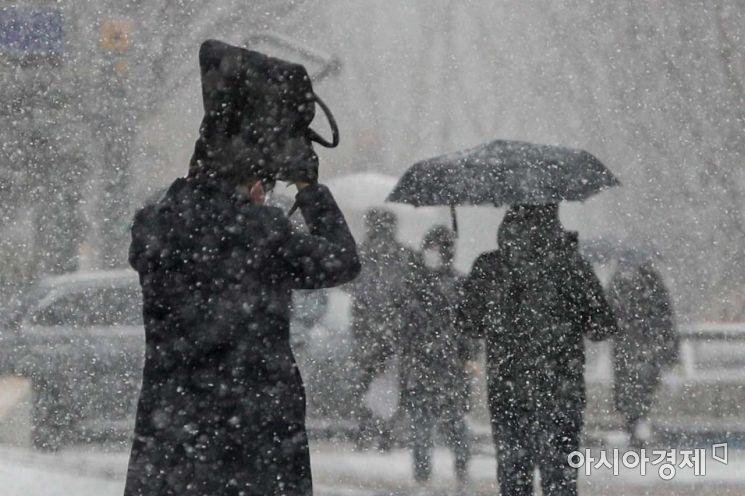 지난 18일 서울 중구 태평로에서 시민들이 내리는 눈을 맞으며 이동하고 있다./강진형 기자aymsdream@