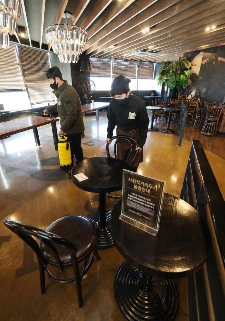 매장 이용 허가를 하루 앞둔 17일 오후 대구 달서구 이월드 내 카페에서 직원들이 방역작업과 더불어 치웠던 의자를 테이블마다 다시 놓고 있다. <이미지:연합뉴스>