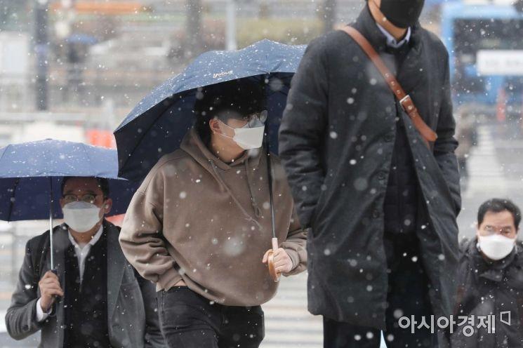전국 곳곳에 대설주의보가 내려진 18일 서울역에서 시민들이 눈을 맞으며 이동하고 있다.