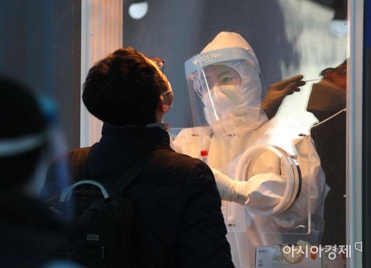 19일 서울역 광장에 마련된 신종 코로나바이러스 감염증(코로나19) 임시 선별검사소에서 의료진이 검체 채취를 하고 있다. 20일은 국내에서 코로나19 첫 확진자가 나온 지 꼭 1년째가 되는 날이다./김현민 기자 kimhyun81@