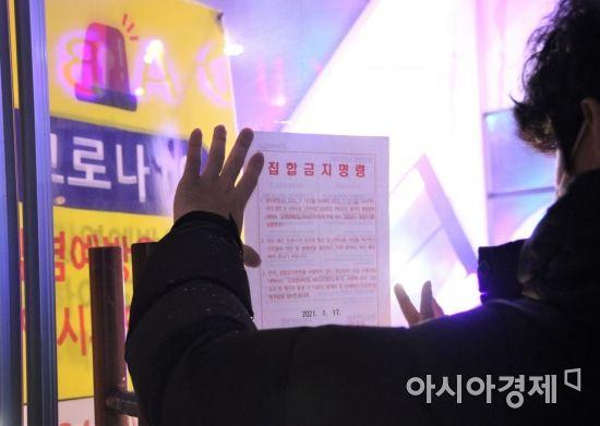 광주광역시 서구 공무원이 집합금지명령문을 유흥업소 입구에 붙이고 있다.
