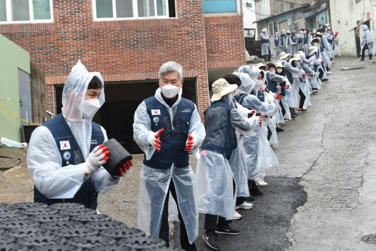 부경대 장영수 총장과 교직원, 학생들이 22일 부산 남구 문현동 일대에서 '사랑의 연탄 나눔 봉사' 활동을 벌이고 있다.