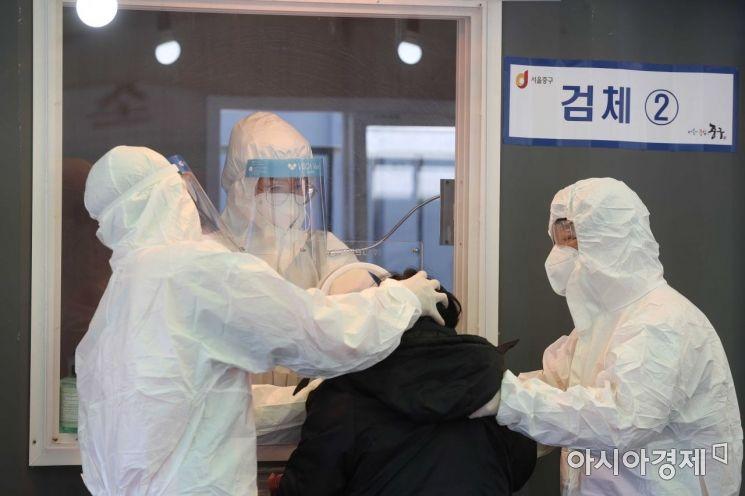 지난 24일 서울역 광장에 마련된 임시 선별검사소에서 의료진이 검체 채취를 하고 있다. /문호남 기자 munonam@