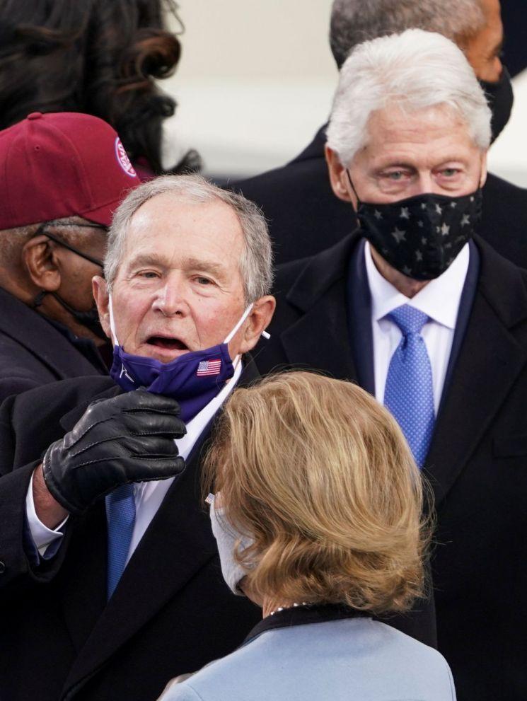 조지 부시 전 미국 대통령이 조 바이든 미국 대통령 취임식 중 갑갑한 듯 마스크를 내리고 있다. [이미지출처=로이터연합뉴스]