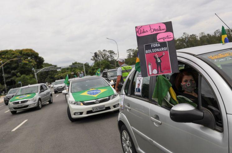 """24일(현지시간) 상파울루의 한 길거리에서 """"브라질 국민의 생명은 소중하다. 보우소나루는 퇴진하라""""라는 내용의 피켓을 들고 차량 시위를 벌이고 있다. 상파울루(브라질)=로이터·연합뉴스"""