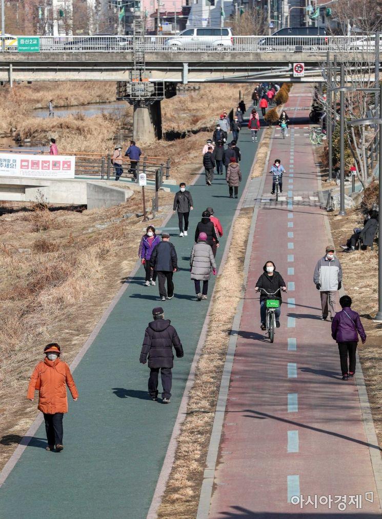 서울 한 낮 기온이 13도까지 상승하며 평년 기온보다 높은 포근한 날씨가 이어지고 있는 25일 서울 서대문구 불광천을 찾은 시민들이 가벼운 옷차림으로 산책을 즐기고 있다./강진형 기자aymsdream@