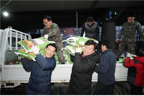 지난해 얼굴 없는 천사가 보낸 20kg 쌀 300포를 실은 트럭이 월곡2동 주민센터 앞에 멈추자 이승로 성북구청장(앞 왼쪽)을 비롯 공무원, 주민, 지역관계자 등이 함께 쌀을 내리고 있다.