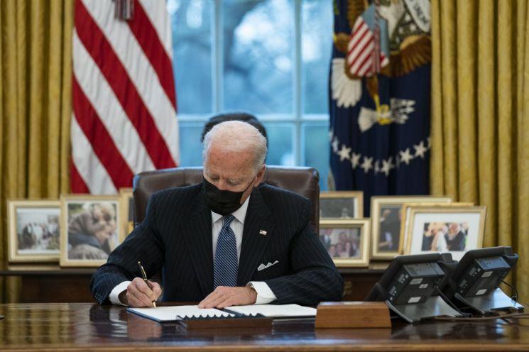 25일(현지시간) 조 바이든 미국 대통령이 자신의 백악관 집무실에서 트랜스젠더의 군 복무를 허용하는 행정명령에 서명하고 있다. 워싱턴(미국)=AP연합