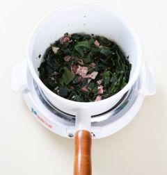 2. 냄비에 참기름을 두르고 쇠고기와 다진 마늘을 넣어 센 불에 3분 정도 볶다가 미역을 넣어 볶는다.