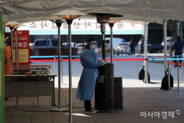 27일 서울광장에 마련된 신종 코로나바이러스 감염증(코로나19) 임시 선별검사소에서 의료진이 난로에 손을 녹이고 있다. /문호남 기자 munonam@