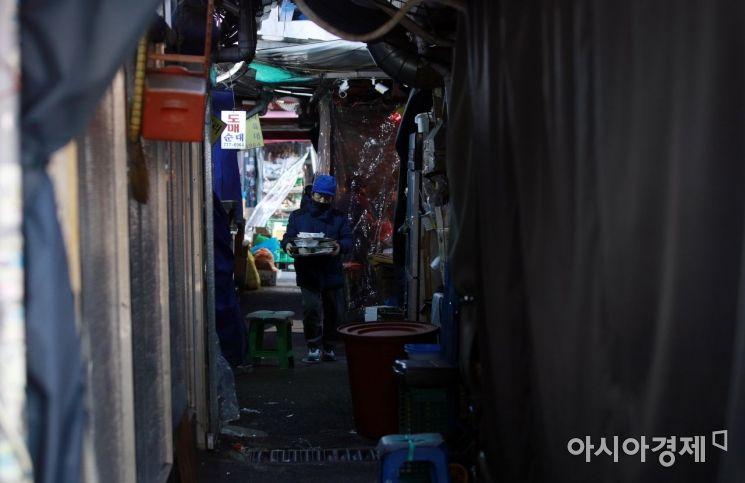 설 연휴를 사흘 앞둔 지난 2월8일 서울 남대문시장 식당 골목에서 한 상인이 음식 배달을 하는 모습./김현민 기자 kimhyun81@