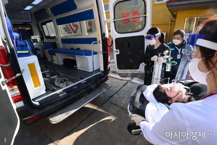 지난 9일 오후 서울 중구 국립중앙의료원 종합암예방접종센터에서 열린 백신 접종 모의 훈련에서 의료진들이 접종을 마친후 이상반응을 보인 참자자를 응급처치후 구급차로 옮기고 있다. /사진공동취재단