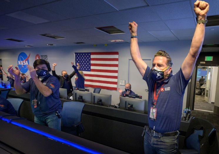 18일(현지시간) 화성탐사선 '퍼서비어런스'호의 화성 착륙 성공 직후 미국 캘리포니아주의 패서디나시에 위치한 미 항공우주국(NASA) 제트추진연구소에서 연구원들이 환호성을 지르고 있다. 패서디나(미국)=EPA연합