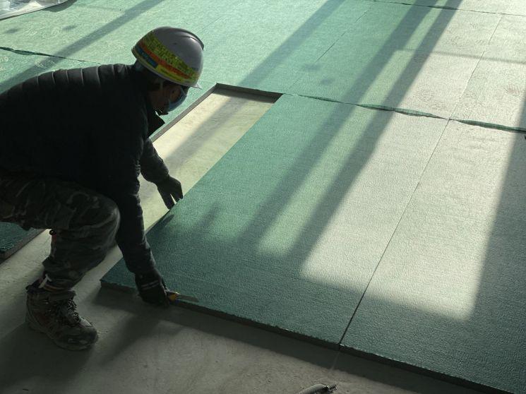 롯데건설은 2015년 롯데케미칼의 스티로폼 단열재와 고무 재질의 완충재 소재를 활용한 60mm 두께의 최고등급 층간소음 완충재 개발에 성공한 바 있다. 사진은 당시 개발한 완충재를 시공하는 모습.
