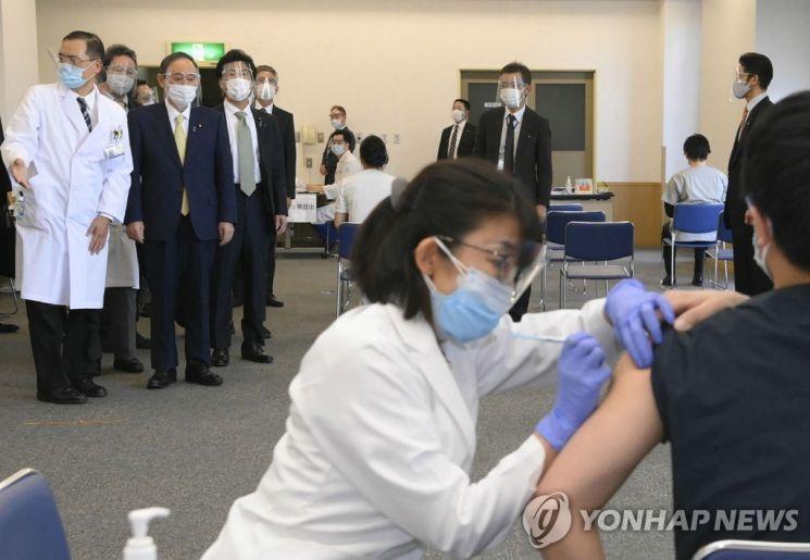 스가 요시히데(위 왼쪽 2번째) 일본 총리가 18일(현지시간) 도쿄에 있는 국영 도쿄 메디컬 센터에서 신종 코로나바이러스 감염증(코로나19) 백신 접종 모습을 지켜보고 있다, 일본은 전날 화이자 백신으로 코로나19 예방접종을 시작했다. / 사진=연합뉴스