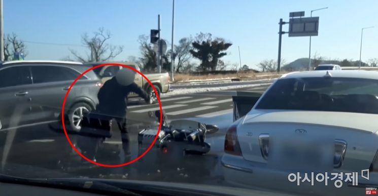 '위험한 추월'에 항의했다가 도로 한복판에서 넘어진 채로 무차별 폭행을 당하는 피해자. 사진=한문철TV 캡처