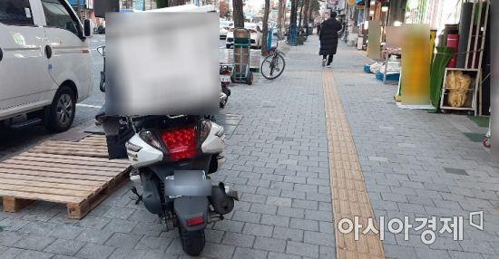 한 배달 오토바이가 시각장애인 유도블록(노랑색) 좌측에 주차되어 있다. 시각장애인 입장에서는 오토바이에 걸려 넘어지거나 큰 사고로 이어질 수 밖에 없다. 사진=한승곤 기자 hsg@asiae.co.kr