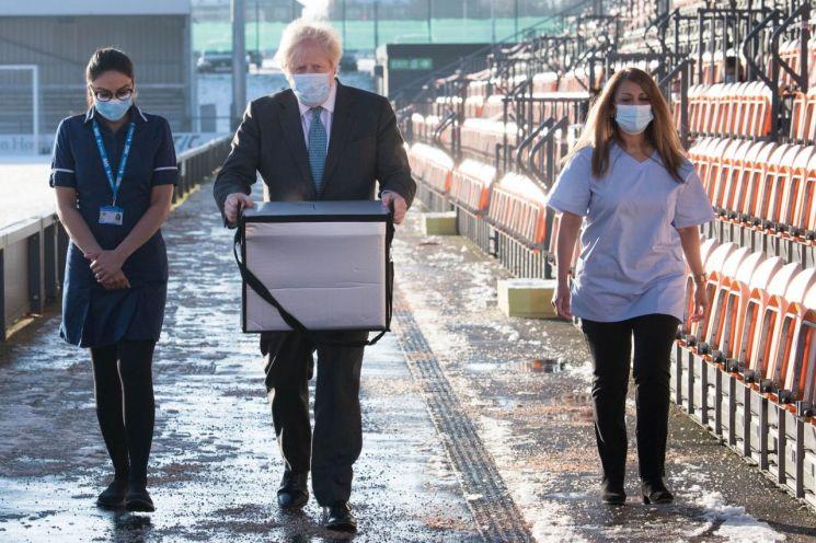 지난달 25일(현지시간) 보리스 존슨(중앙) 영국 총리가 런던 북쪽 바넷FC의 홈구장 '더 하이브'에 마련된 코로나19 백신 접종 센터에서 코로나19 백신이 든 상자를 옮기고 있다. [이미지출처=로이터연합뉴스]