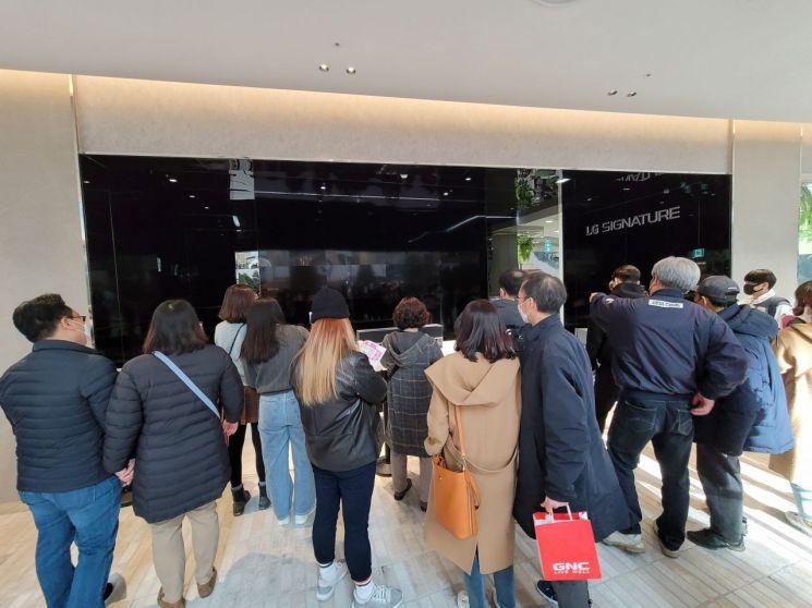 본체 속으로 화면을 말아넣는 LG 롤러블 TV를 보기 위해 모여든 사람들/사진=우수연 기자