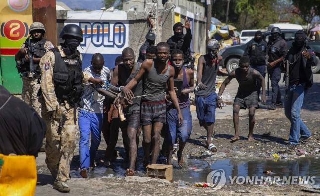 25일(현지 시각) 탈옥했다 다시 붙잡힌 아이티 교도소 수감자들  [AP=연합뉴스]/ 사진 = 연합뉴스