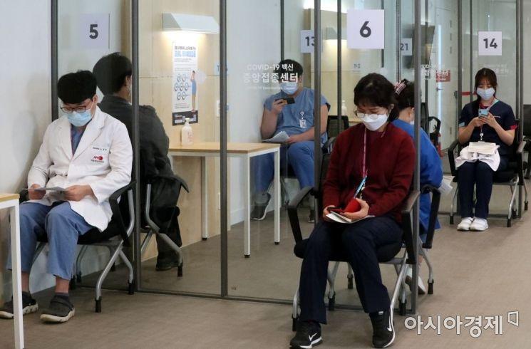 27일 오전 서울 중구 국립중앙의료원 중앙예방접종센터에서 코로나19 화이자 백신 1차 접종이 시작되면서 주사를 맞은 의료 종사자들이 관찰실에서 대기하고 있다. 이날 국립중앙의료원에서 의료진, 종사자 199명이 화이자 백신 접종을 받는다. /사진공동취재단