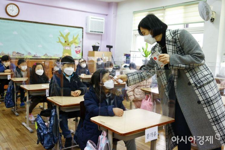 서울의 한 초등학교에서 담임교사가 등교한 학생들의 열을 측정하고 있다./사진공동취재단