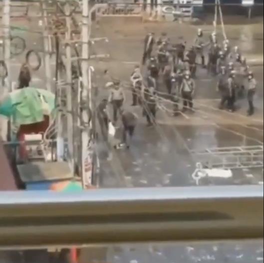 총에 맞아 숨진 시민을 경찰 2명이 끌고 가는 모습. 베란다에서 찍은 듯 철제 구조물이 화면 아래 보인다.[트위터 캡처]