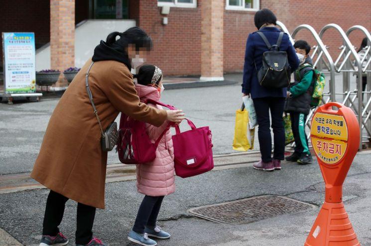 광주 서구 한 초등학교에서 학부모들이 등교하는 학생들을 교문 앞에서 배웅하고 있다. 사진은 기사 중 특정 표현과 무관. [이미지출처=연합뉴스]