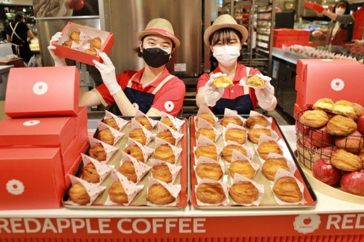 9일 서울 중구 롯데백화점 본점 지하 1층에서 직원들이 '레드애플 팝업스토어'를 홍보하고 있다.