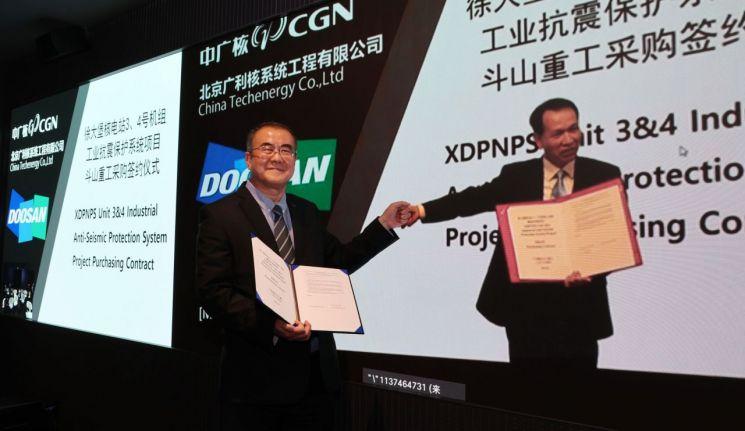 두산중공업 나기용 부사장(사진 왼쪽)과 중국 CTEC 장궈진 사장이 화상으로 계약을 체결한 뒤 주먹 인사를 하고 있다.(사진제공 = 두산중공업)