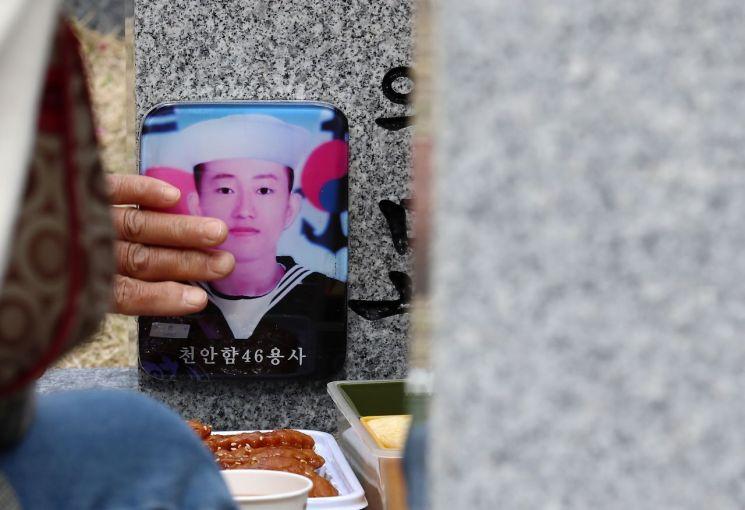 국립대전현충원 천안함 46용사 묘역에서 고(故) 강현구 하사 유가족이 묘비를 정돈하고 있다. [이미지출처=연합뉴스]