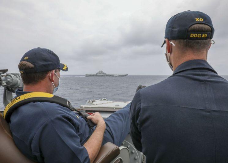 지난 4일(현지시간) 필리핀 인근 해역에 배치된 미국 구축함 USS 머스틴 갑판 위에서 함장 로버트 J 브릭스(왼쪽)와 부함장 리처드 D 슬라이(오른쪽)이 중국 측 랴오닝 항공모함 전단을 바라보고 있다. [사진출처=미 해군]