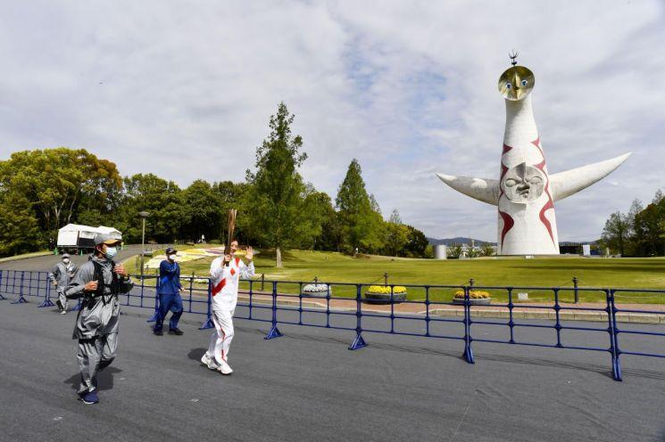 일본의 전 여자 배영 선수인 데라가와 아야가 13일 오사카현 엑스포 70 기념공원에서 관중이 없이 도쿄올림픽 성화를 봉송하고 있다./사진=연합뉴스