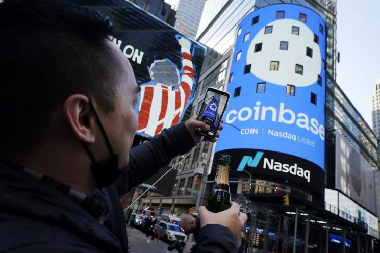 코인베이스의 직원이 한 손에 샴페인을 들고 나스닥 시장 건물 대형 전광판에 뜬 코인베이스 로고를 사진으로 찍고 있다. [이미지출처=AP연합뉴스]