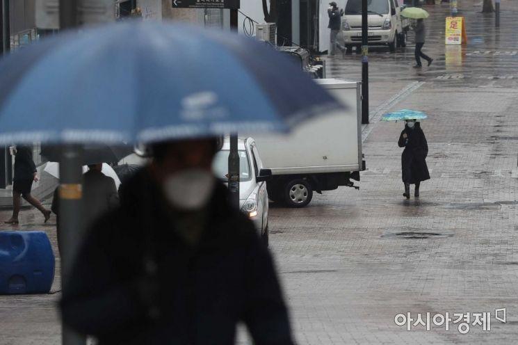 초봄 같은 포근한 날씨 속 비가 내린 26일 서울 명동에서 우산을 쓴 시민들이 발걸음을 재촉하고 있다. /문호남 기자 munonam@