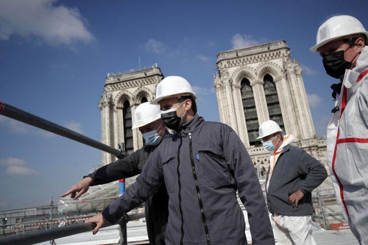 에마뉘엘 마크롱 프랑스 대통령이 15일(현지시간) 파리 노트르담 대성당 복구 현장을 돌아보고 있다. [이미지출처=AP연합뉴스]