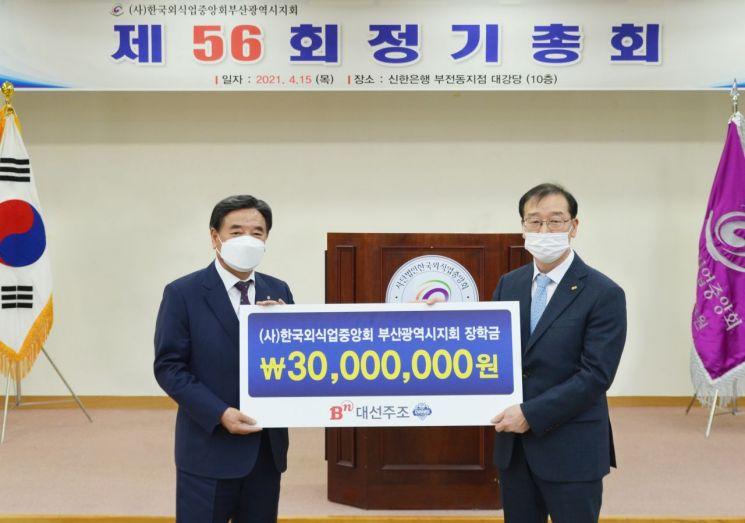 대선주조 차재영 상무이사가 4월 15일 한국외식업중앙회 강인중 부산시지회장에게 장학금을 전달하고 있다. [이미지출처=대선주조]