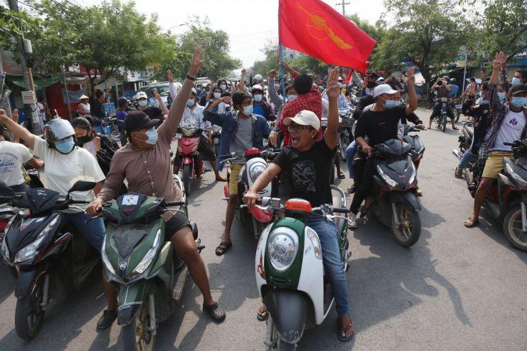 미얀마 지방도시 만달레이에서 15일(현지시간) 오토바이를 탄 시위대가 군부 쿠데타를 규탄하며 저항의 표시로 세 손가락 경례를 하고 있다. [이미지출처=연합뉴스]