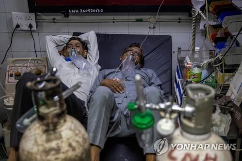 인도 뉴델리 LNJP 병원에서 두 명의 코로나19 환자가 한 침대에서 치료 받고 있다. [이미지출처=연합뉴스]